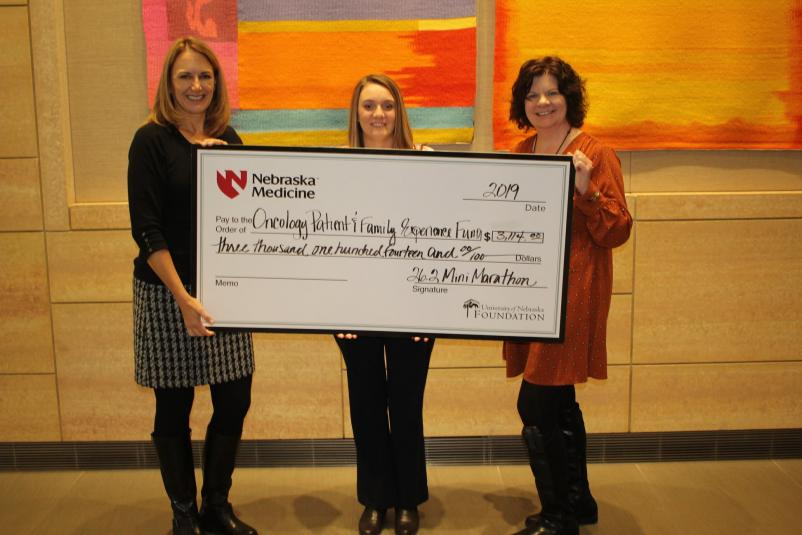 Denise Ibsen Cole presents a $3,114 check to oncology social workers Angela and Rachelle.