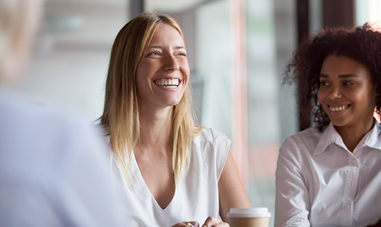 Two women smiling and talking over coffee.