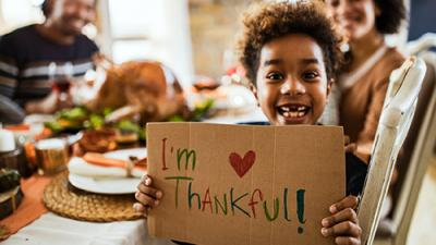 "A child holding an ""I'm thankful!"" sign."