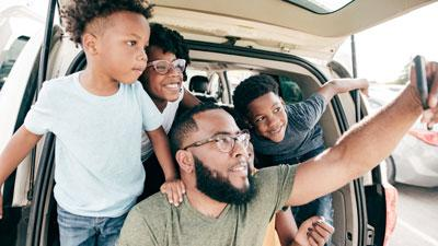Black family on a road trip taking a selfie picture together